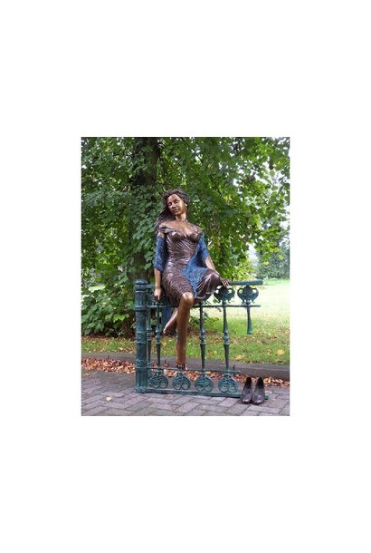 Frau sitzt auf dem Zaun