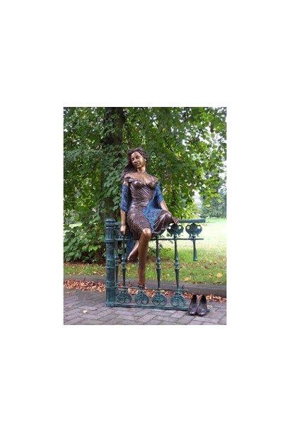 Vrouw zittend op hek