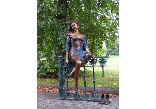 BronzArtes Frau sitzt auf dem Zaun