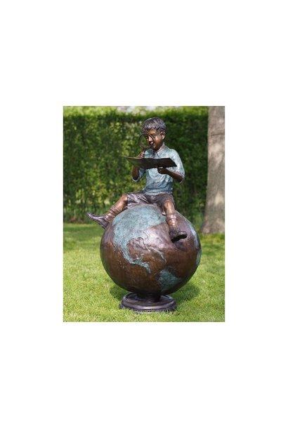 Boy sitting on globe