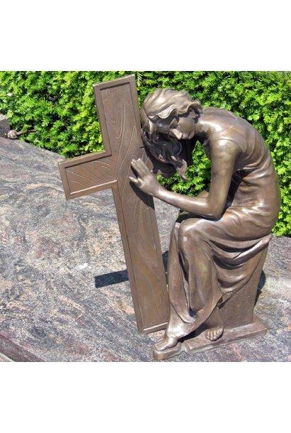 Girl sitting beside cross