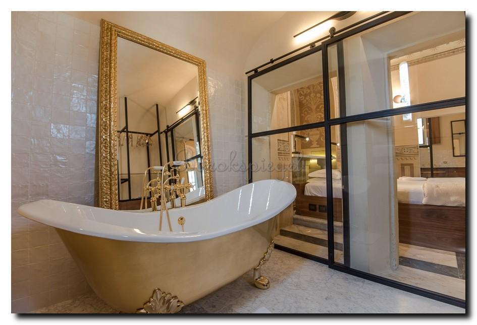 Grote gouden Italiaanse vloerspiegel in badkamer