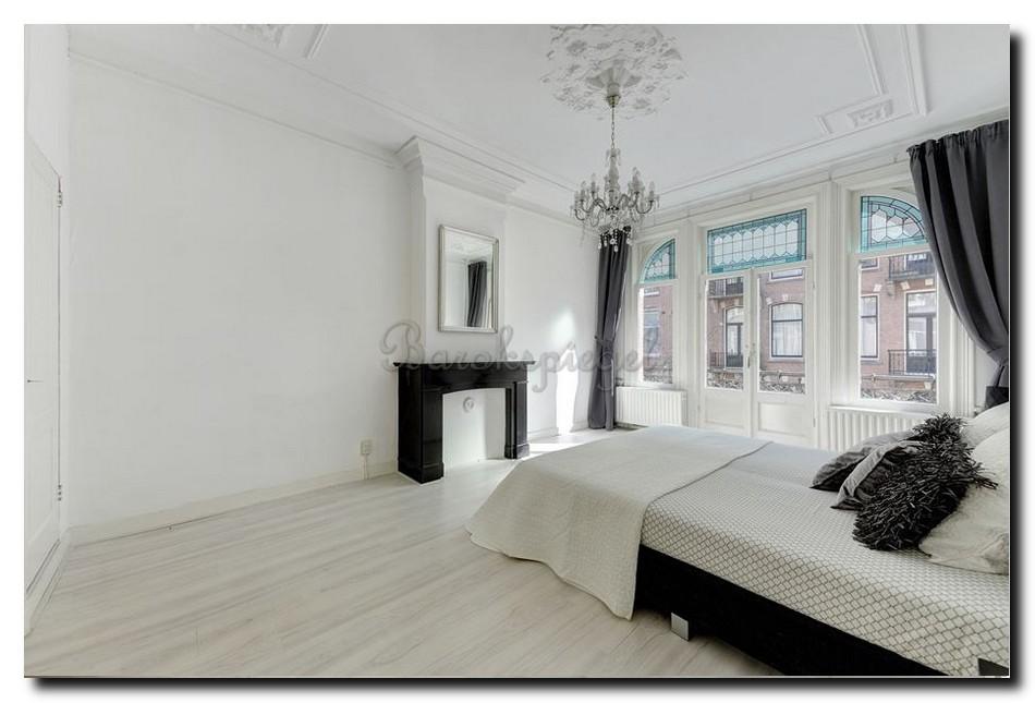 zilveren spiegel op schouw in minimalistische slaapkamer
