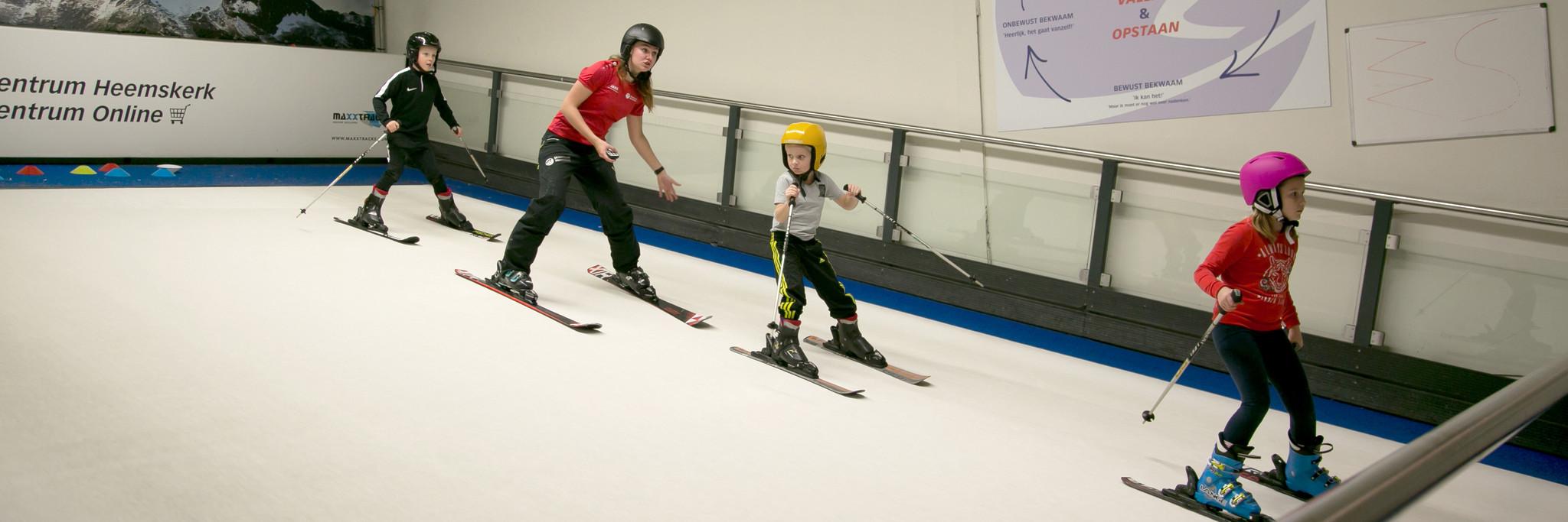 Kinderen krijgen skiles op de indoorrolbaan bij Skicentrum Heemskerk