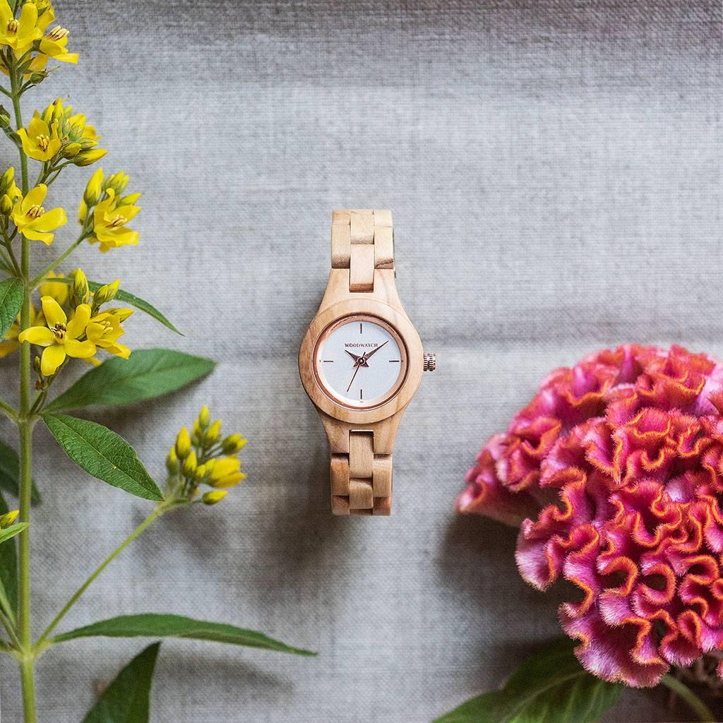 Blossom uret fra Flora Kollektionen er fremstillet af naturligt oliventræ med en håndskåret, slank ramme. Blossom urets cremefarvede urskive er af rustfrit stål og har et funklende udseende med detaljer i rosenguld.