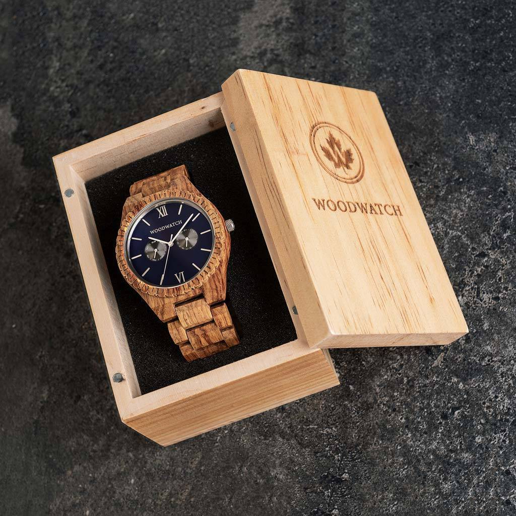 Denna premiumdesignade klocka kombinerar ett unikt träslag med en lyxig bakboett i rostfritt stål och en admiralblå urtavla. I hjärtat av klockan slår ett multifunktionellt urverk med två extra urtavlor för vecka och månad. GRAND Ocean Blue är tillverkad