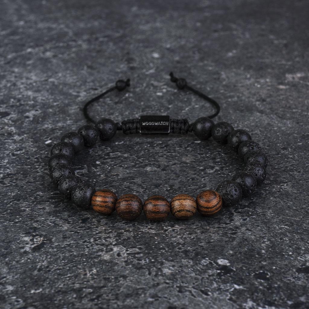 Vores håndlavede Rosewood Volcanic Beads Bracelet er fremstillet i en kombination af 8 mm perler i palisander og vulkansk sten. Armbåndet er justerbart og passer til de fleste håndled. En perfekt accessory til dit WoodWatch.