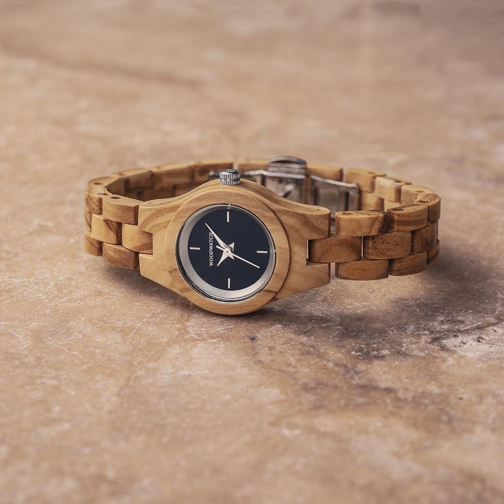 Iris-klockan från FLORA Collection består av mjukt oliv-trä som har handarbetats till att bli otroligt tunt. Iris har en midnattblå urtavla med silver-färgade detaljer.