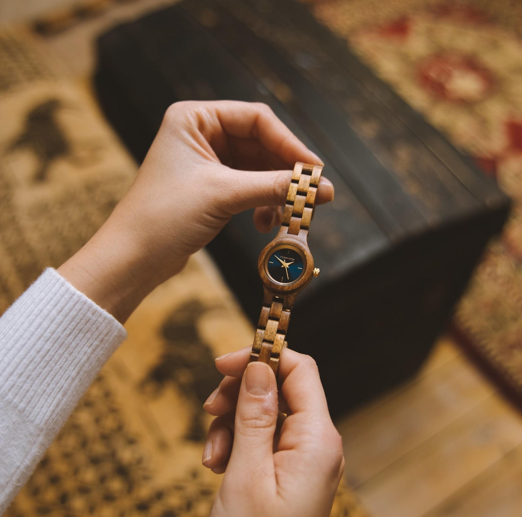 Uret Bellflower fra FLORA Collection er lavet i blødt akacie træ, der er håndlavet med det fineste, slanke design. Bellflower har en mørk marineblå urskive med gyldne detaljer.