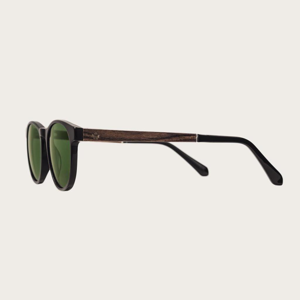 ELLIPSE Black Camo har en karakteristiskt avrundad svart båge med gröna kamoflagefärgade linser. Gjorda av hållbart italienskt Mazzucchelli bio-acetat med handbehandlade naturliga skalmar av rosenträ och svarta ändar av acetat. Bioacetat är tillverkat av