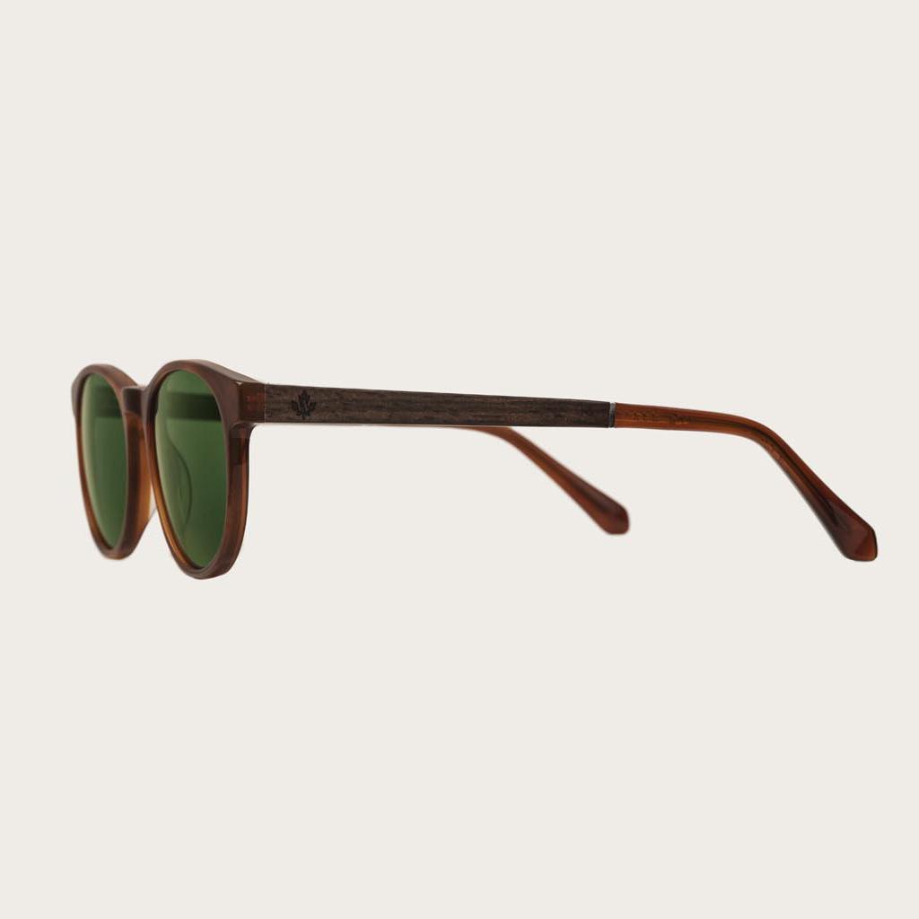 ELLIPSE Classic Havanas Camo har en karakteristiskt avrundad mörkgult sköldpaddsmönstrad båge med gröna kamoflagefärgade linser. Gjorda av hållbart italienskt Mazzucchelli bio-acetat med handbehandlade naturliga skalmar av ebenholts och sköldpaddsmönstrad