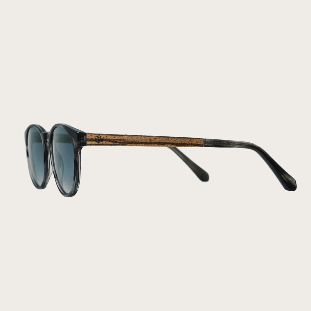 ELLIPSE Heritage Gradient Blue har en karakteristiskt avrundad grå sköldpaddsmöntrad båge med gradientblå linser. Gjorda av hållbart italienskt Mazzucchelli bio-acetat med handbehandlade naturliga skalmar av zebraträ temples och sköldpaddsmönstrade ändar