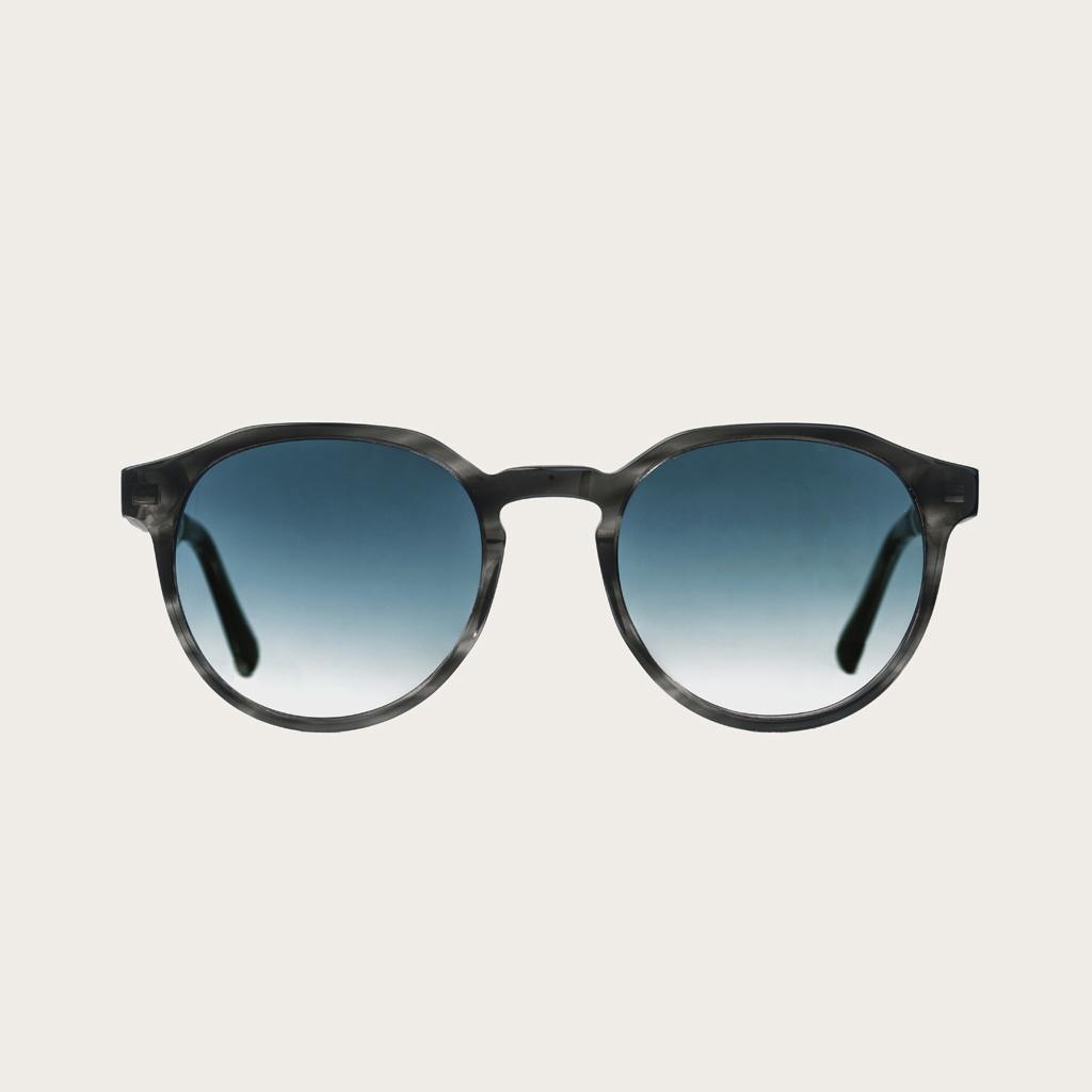 REVELER Heritage Gradient Blue har en stilren geometrisk grå sköldpaddsmöntrad båge med gradientblå linser. Gjorda av hållbart italienskt Mazzucchelli bio-acetat med handbehandlade naturliga skalmar av zebraträ temples och sköldpaddsmönstrade ändar av ace