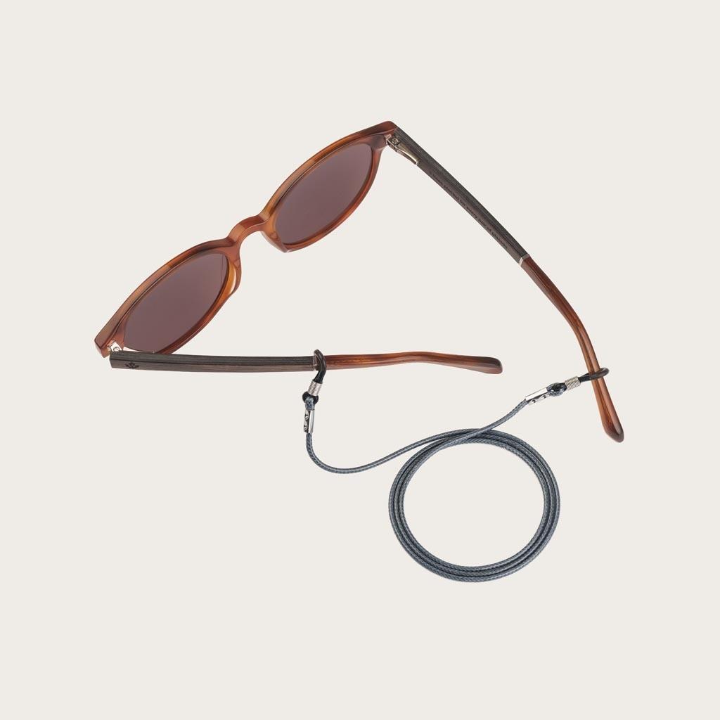 Är du trött på att tappa eller krossa dina glasögon eller solglasögon? Vi skyddar dina glasögon på ett moderiktigt sätt. Utstrålar elegans, denna subtil, grå snodd i läderutseende kan matchas med dina WoodWatch-glasögon eller fäst den till dina egna glasö