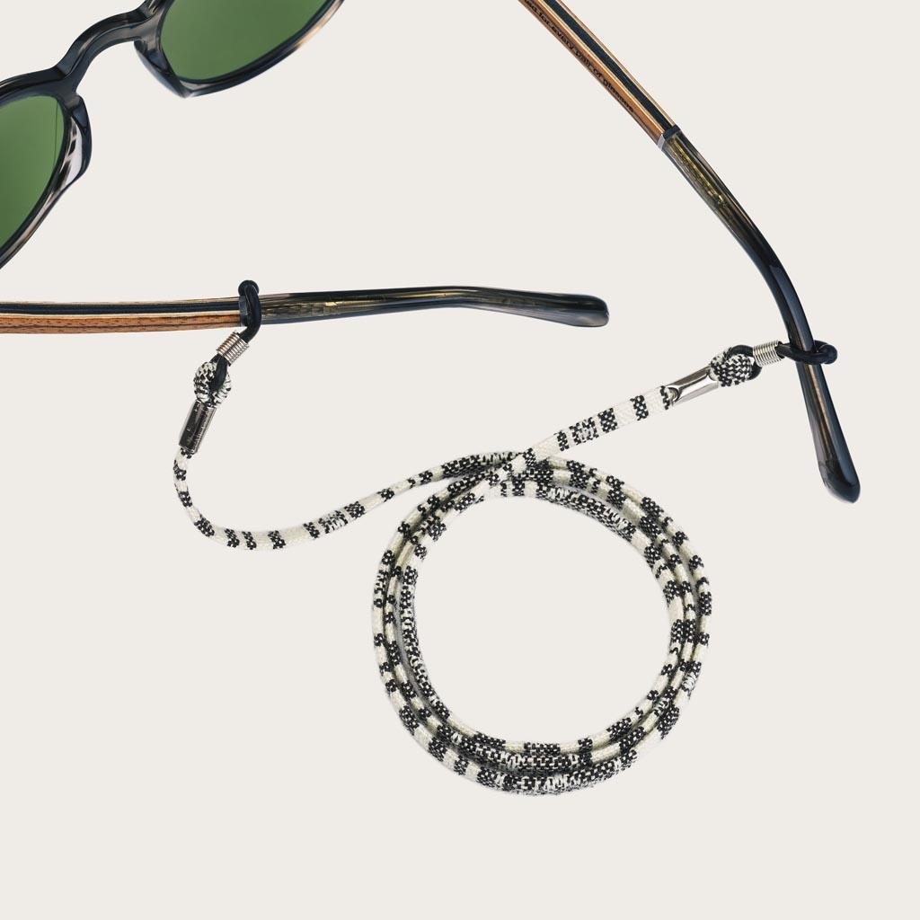 Är du trött på att tappa eller krossa dina glasögon eller solglasögon? Vi skyddar dina glasögon på ett moderiktigt sätt. Utstrålar elegans, denna vit och svart mönstrad snodd kan matchas med dina WoodWatch-glasögon eller fäst den till dina egna glasögon!