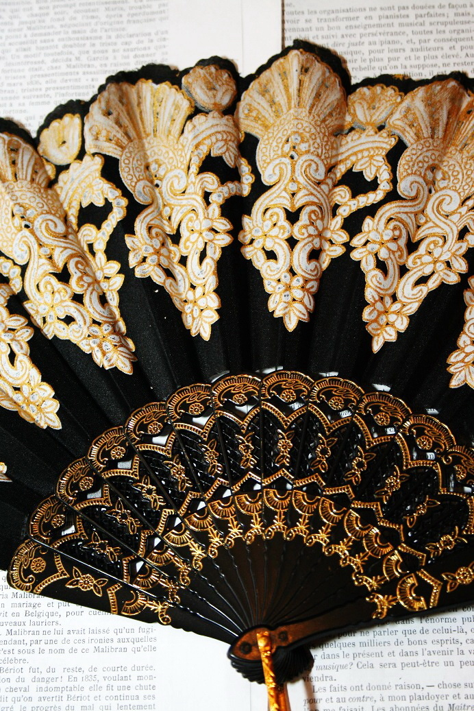 Black fan with gold print.