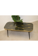 Black glass coffee table with golden stains