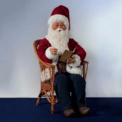 Kerstman zittend op stoel, een boek lezend