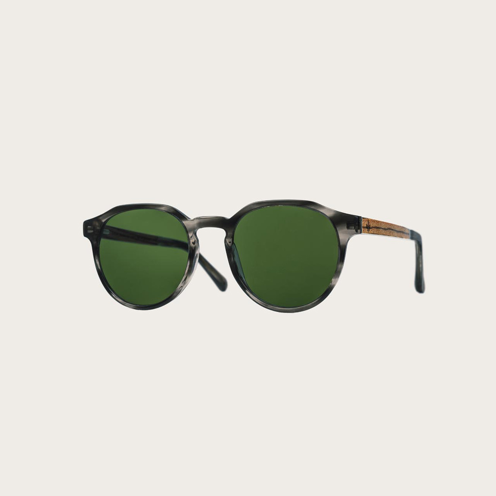 The REVELER Heritage Camo features a sleek geometric grey tortoise frame with green camo lenses. Composed of durable Italian Mazzucchelli bio-acetate with hand-finished natural zebrawood temples and tortoise acetate tips. Bio-acetate is made from cotton a