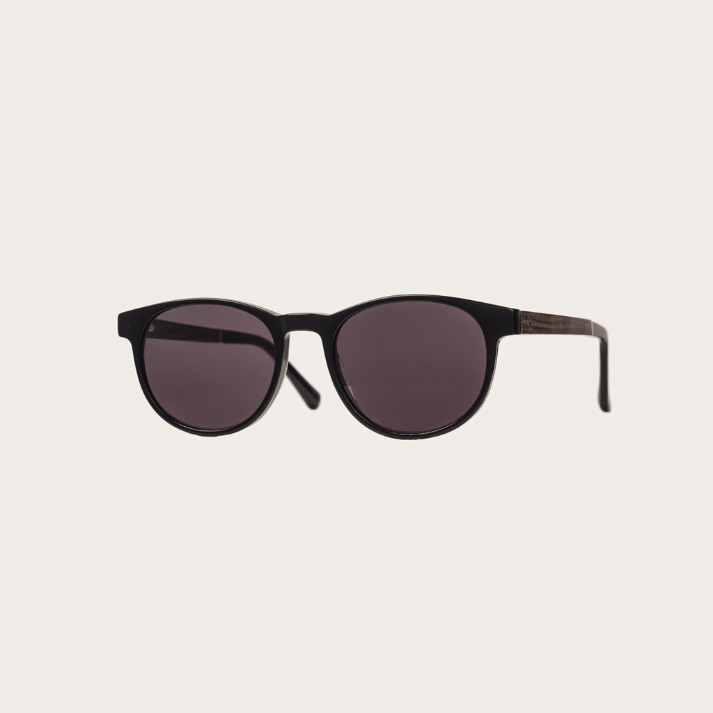 The ELLIPSE All Black features a characteristic rounded black frame with black lenses. Composed of durable Italian Mazzucchelli bio-acetate with hand-finished natural rosewood temples and black acetate tips. Bio-acetate is made from cotton and organic res