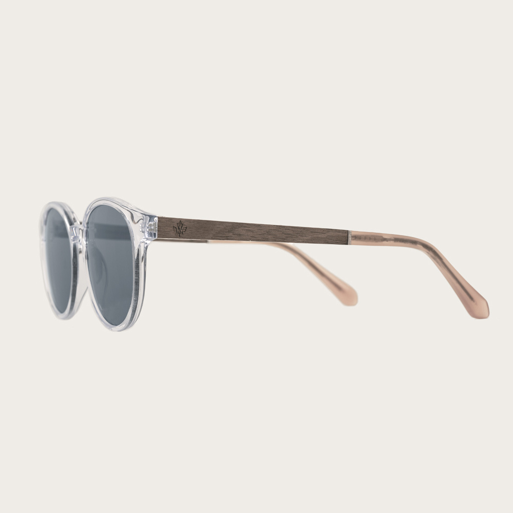 The SOHO Clear Smoke features an oval clear frame with grey smoke lenses Composed of durable Italian Mazzucchelli bio-acetate with hand-finished natural senna siamea wood temples and nude acetate tips. Bio-acetate is made from cotton and organic resins ma