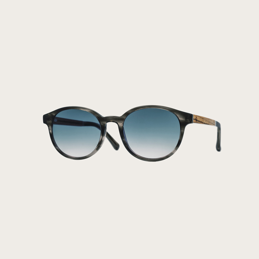 The SOHO Heritage Gradient Blue features an oval grey tortoise frame with gradient blue lenses. Composed of durable Italian Mazzucchelli bio-acetate with hand-finished natural zebrawood temples and tortoise acetate tips. Bio-acetate is made from cotton an