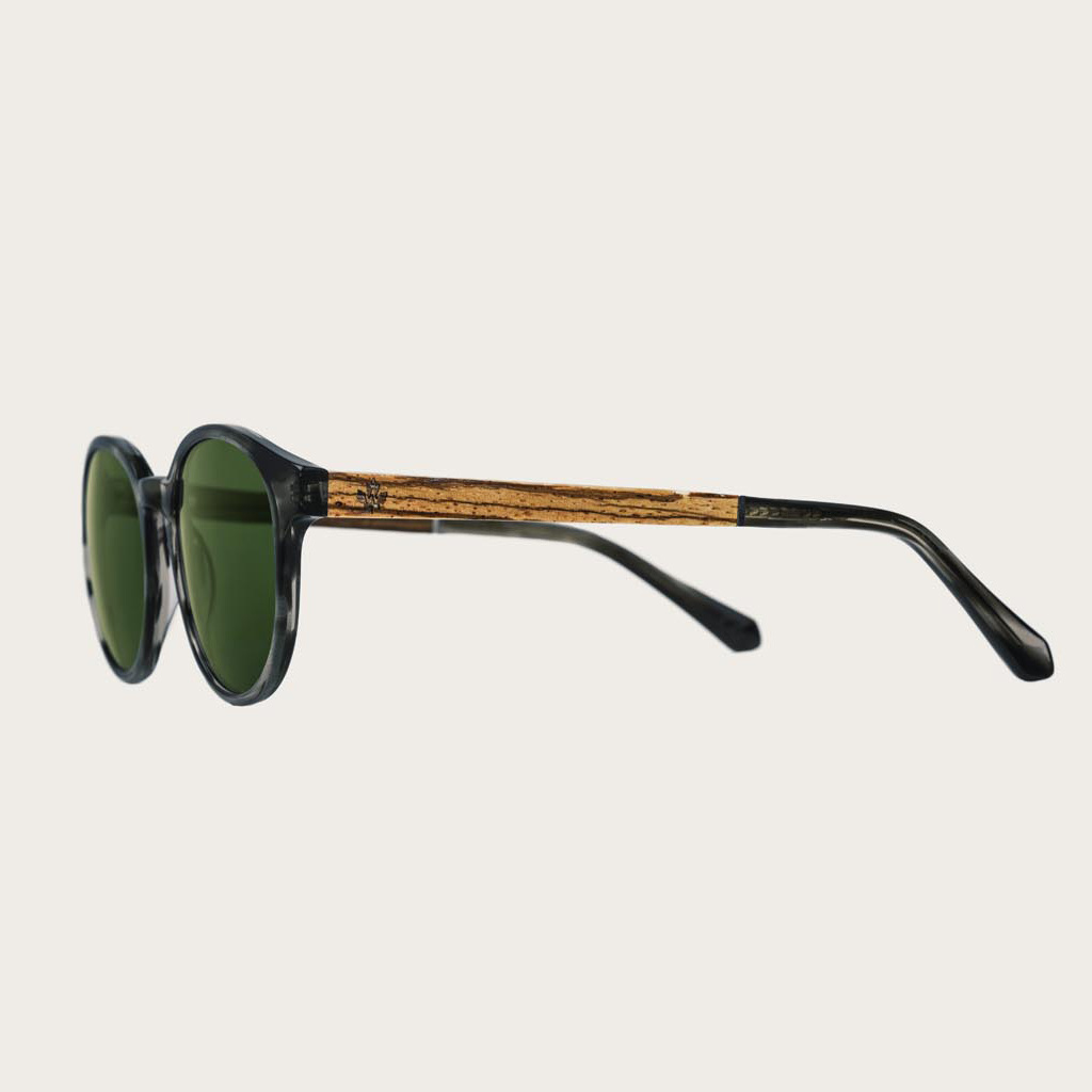 The SOHO Heritage Camo features an oval grey tortoise frame with green camo lenses. Composed of durable Italian Mazzucchelli bio-acetate with hand-finished natural zebrawood temples and tortoise acetate tips. Bio-acetate is made from cotton and organic re