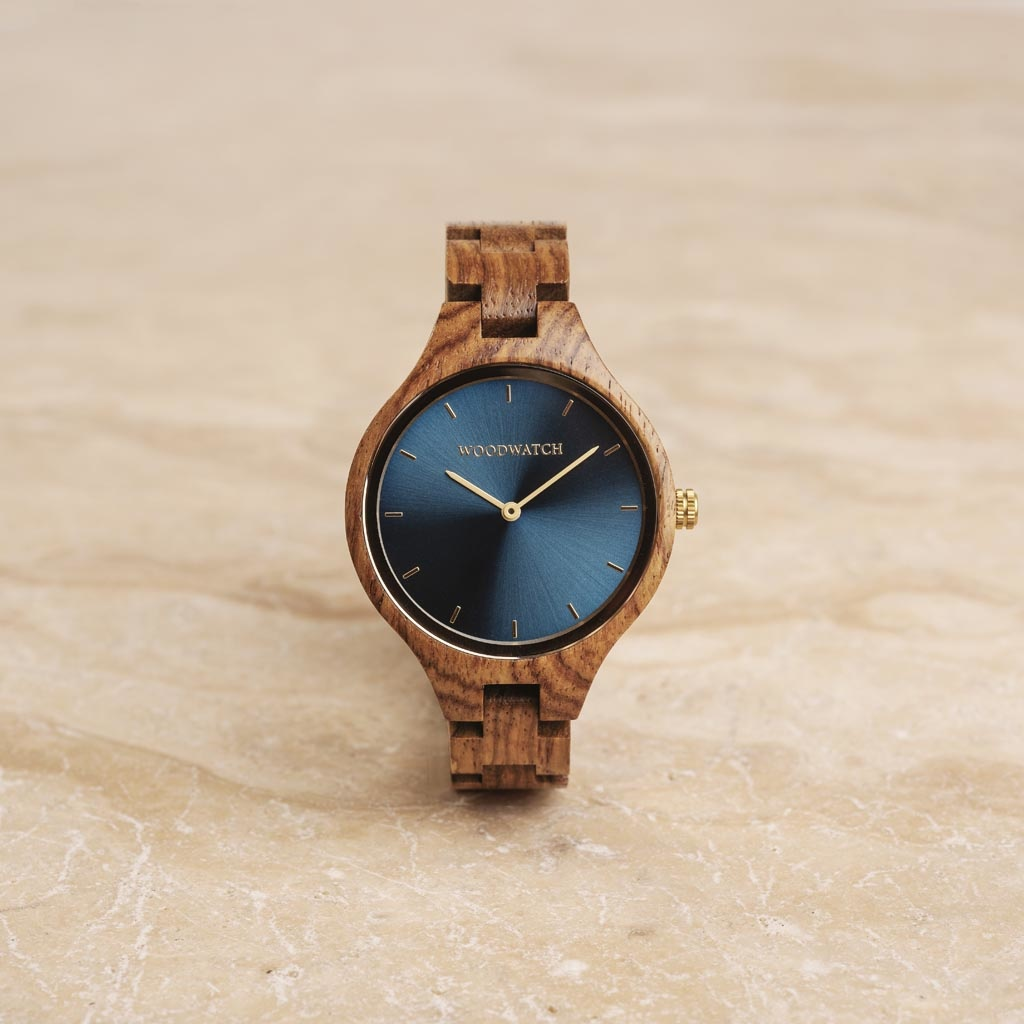 The AURORA Collection breaths the fresh air of Scandinavian nature and the astonishing views of the sky. This light weighing watch is made of kosso wood, accompanied by a blue stainless-steel dial with golden details.<br />