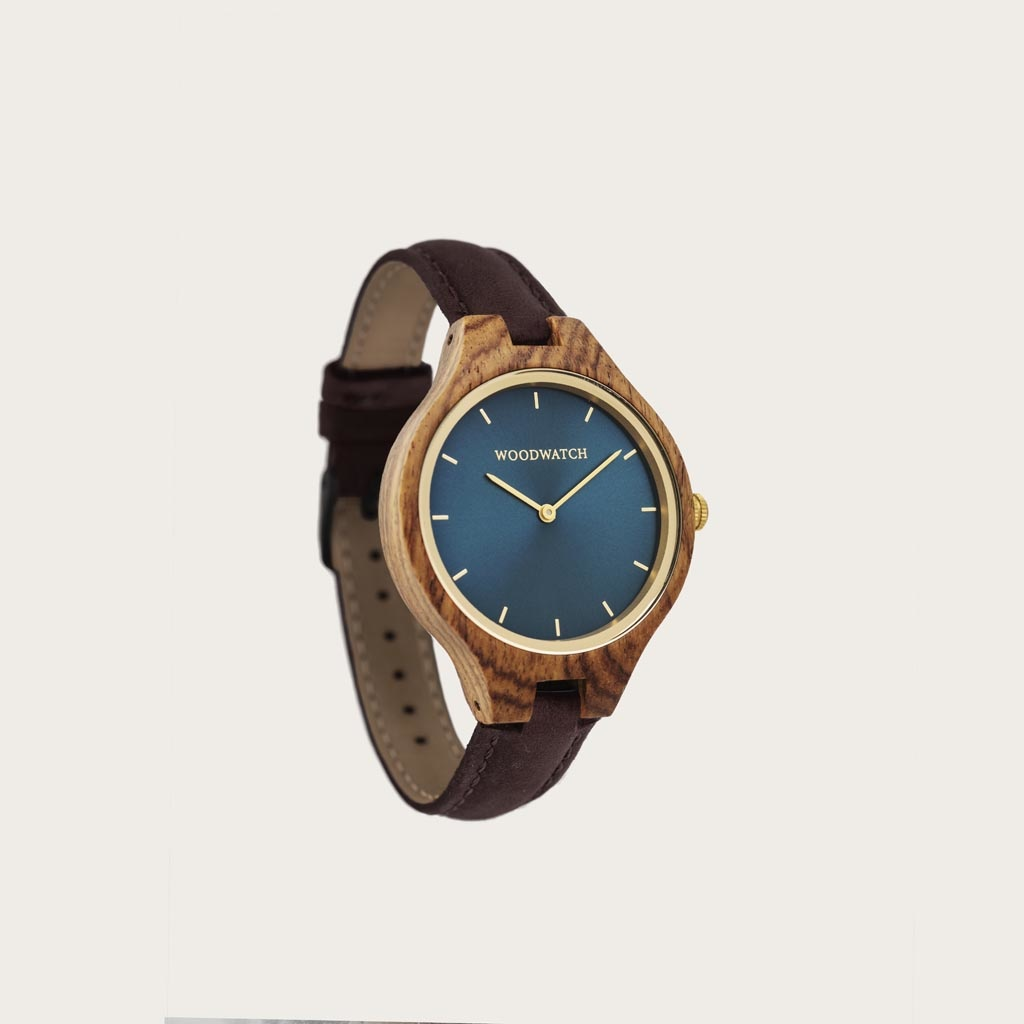 The AURORA Collection breaths the fresh air of Scandinavian nature and the astonishing views of the sky. This light weighing watch is made of kosso wood, accompanied by a blue stainless-steel dial with golden details.<br /> The watch is available with a wooden