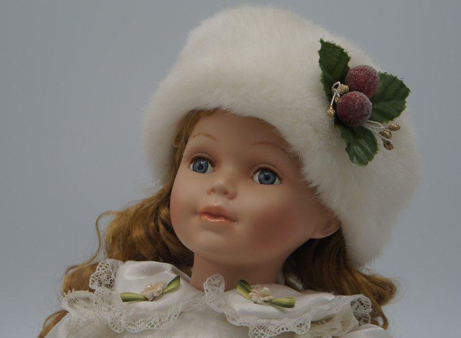 Porcelain doll in white winter dress