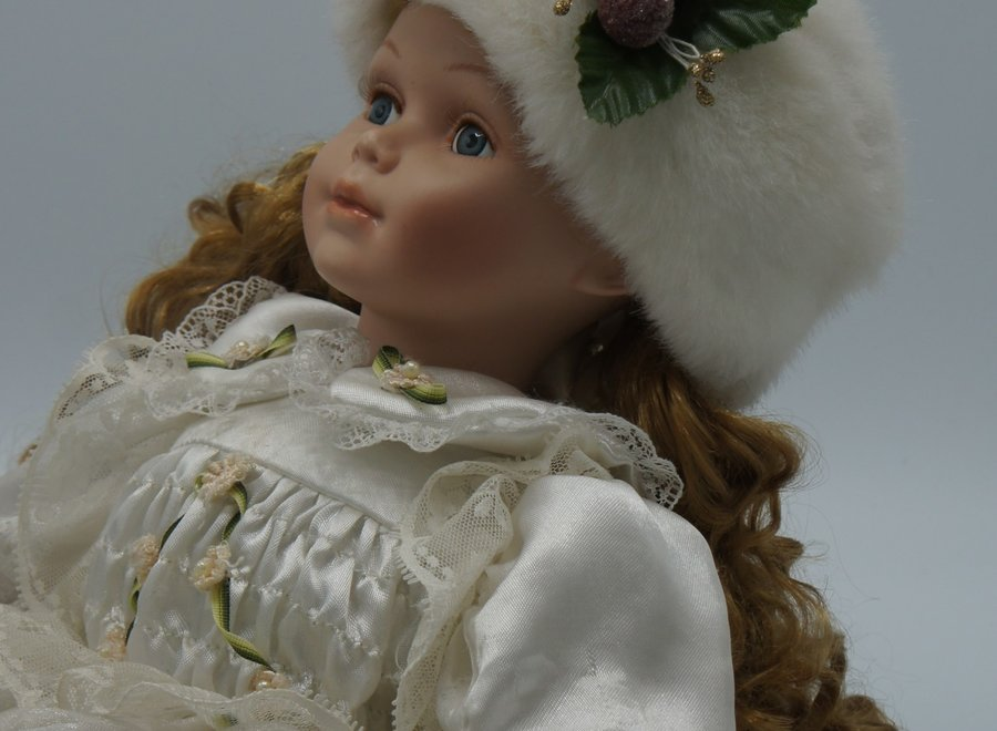 Decoratieve, zittende pop in winterse sfeer.