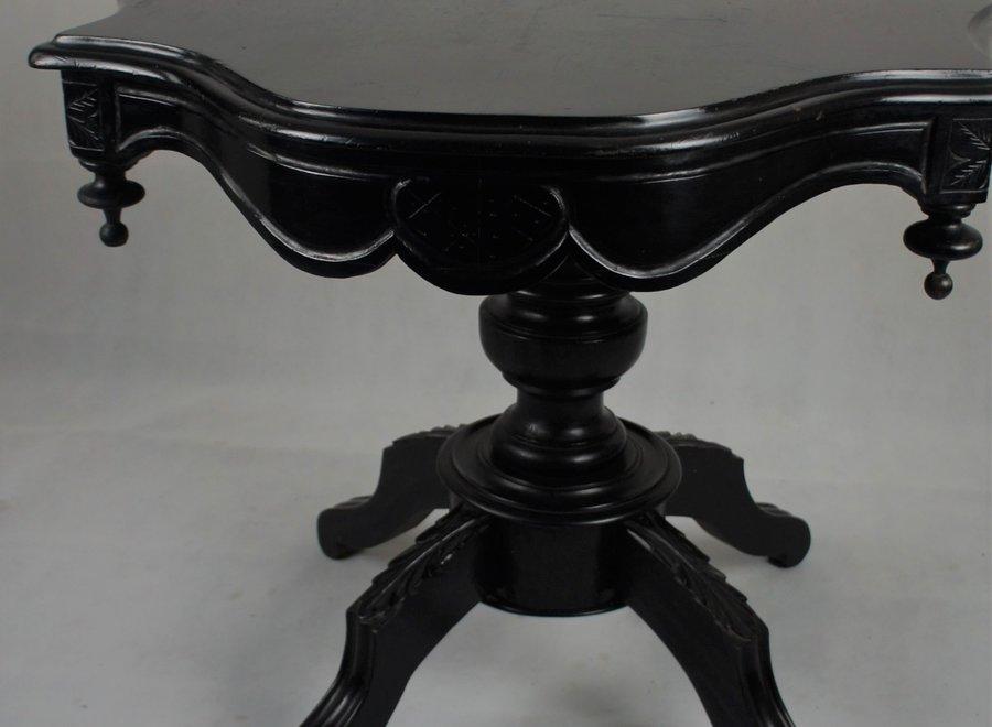 Deze romantische tafel werd enkele jaren geleden gerestaureerd en in het zwart geschilderd.