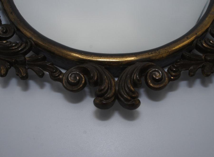 Prachtige sierlijke ovalen bronzen spiegel, bewerkt met krullen.