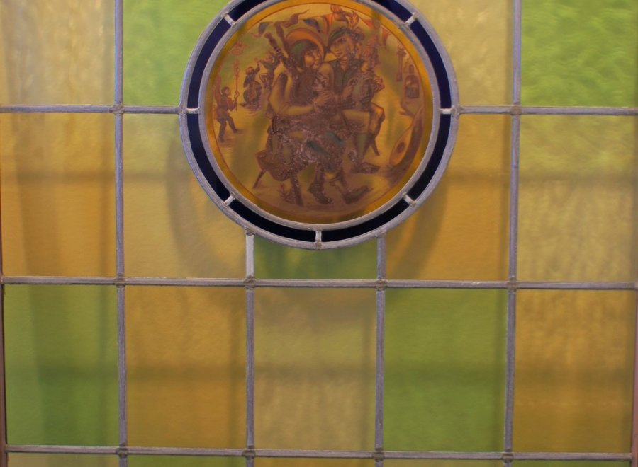 Authentic stained glass window - white, yellow, green with a medieval scene in the middle
