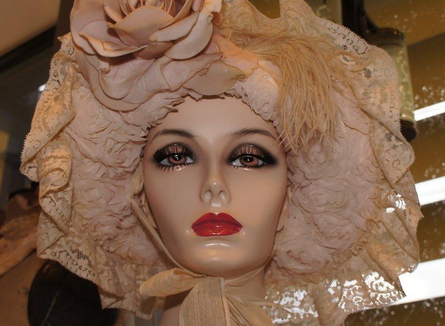 Fleurige hoed afgewerkt met kant en striklint.