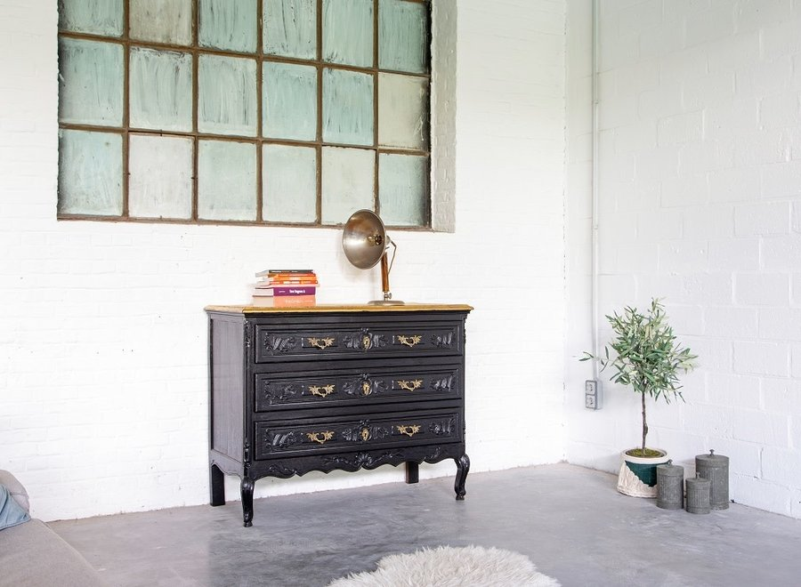 Black patinated chest of drawers with gilt top