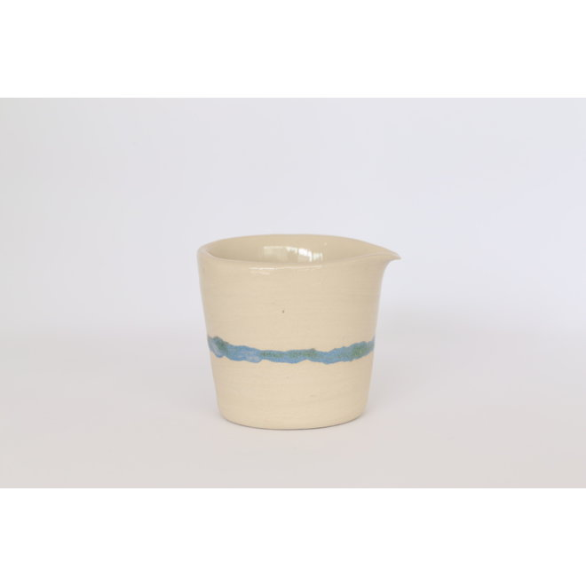Milk jug made of beige clay with a green - blue edge