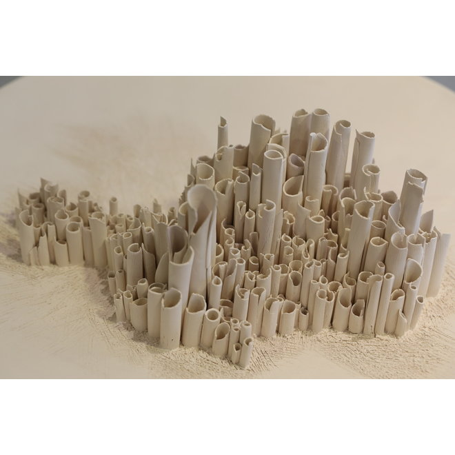 Ceramic art processed on a scale made from earthy clay with unfinished pipes.