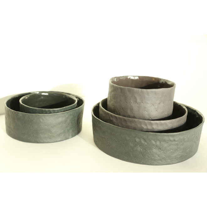 Handmade dishes and pots in black porcelain with a shiny transparent glaze finished.