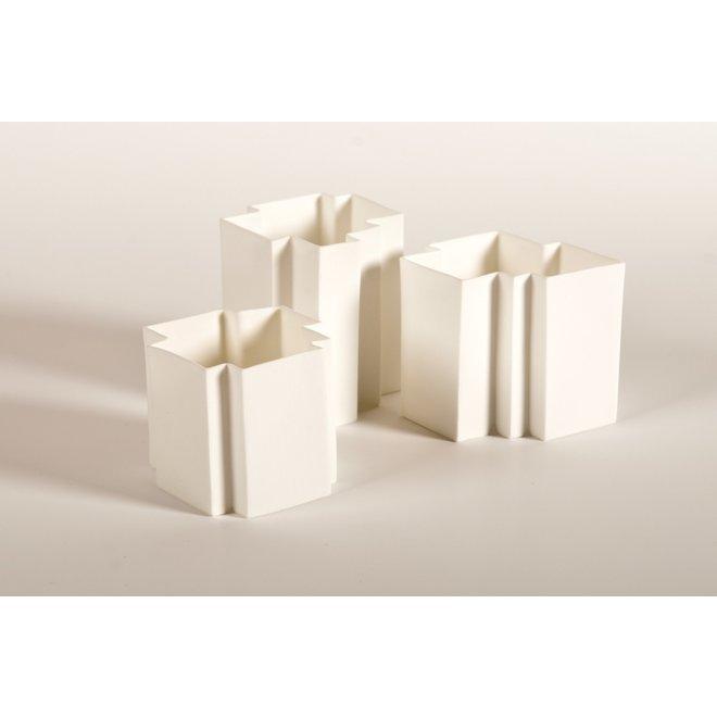 Une bougie chauffe-plat en porcelaine blanche conçue sous forme de casse-tête qui peut être combinée à la perfection et de façon unique