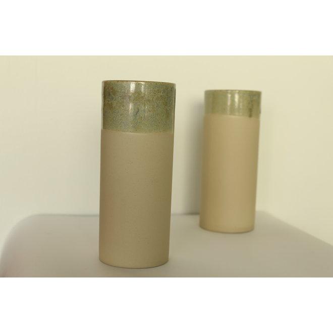 Handgemaakte beige keramische vaas gemaakt in gietklei met een mooi groene rand en siert in zijn eenvoud