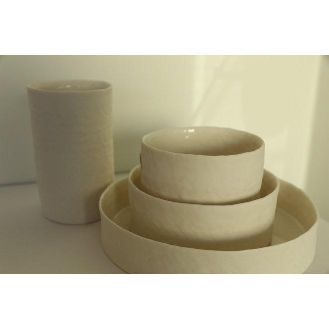 Collectie handgemaakte schalen en kommetjes in porselein met een blinkende transparante glazuur aan de binnenzijde afgewerkt.
