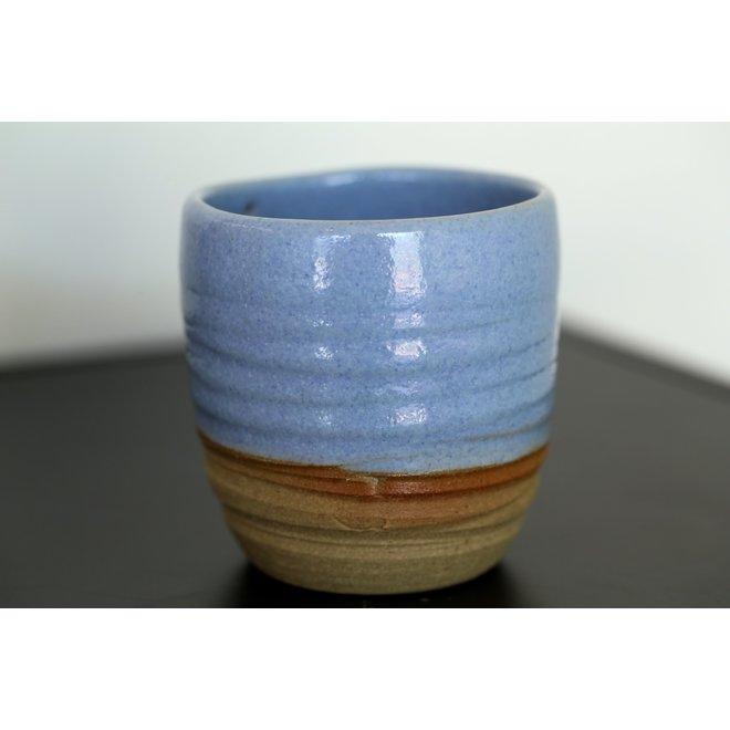 Avec le tasse tourné à la main en argile naturelle fini avec un beau glacis bleu clair à haute cuisson.