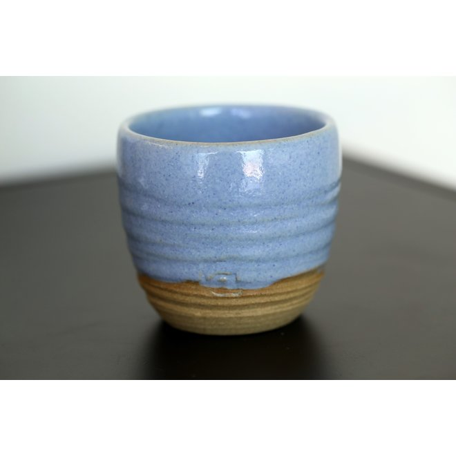 With the turntable handmade cup of natural clay with a beautiful blue high firing glaze.