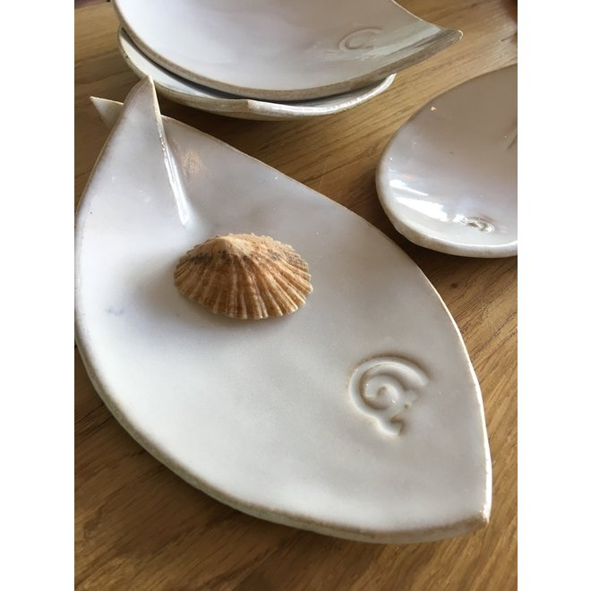 White ceramic scale in the shape of a fish. Original dish for meats, cheese, appetizers, sushi ...