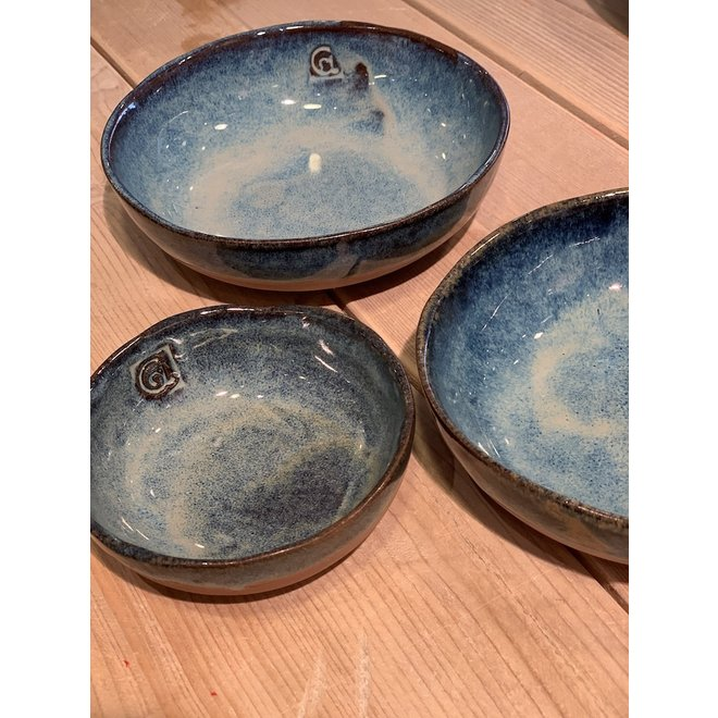 In the mold laid round dish of Belgian clay with a beautiful Floating blue highly fired glaze.