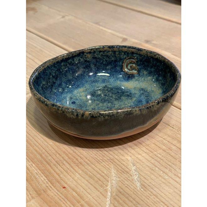 In de mal gelegde ronde schaal van Belgische klei met een mooie Floating blauw hoog bakkende glazuur.