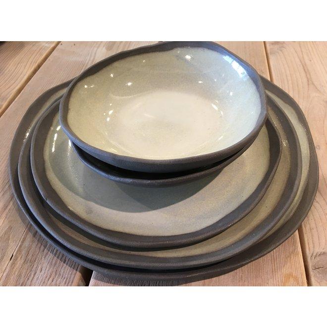 Une assiette de style, ludique et faite spontanément d'argile grise et finie de glaçure verte