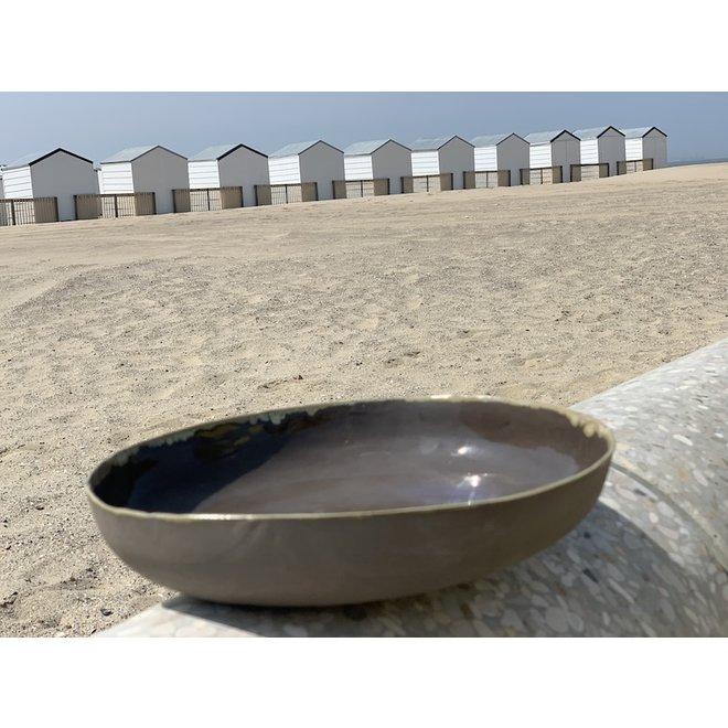 Plat fait main en argile fondue grise avec une touche artistique subtile ocre