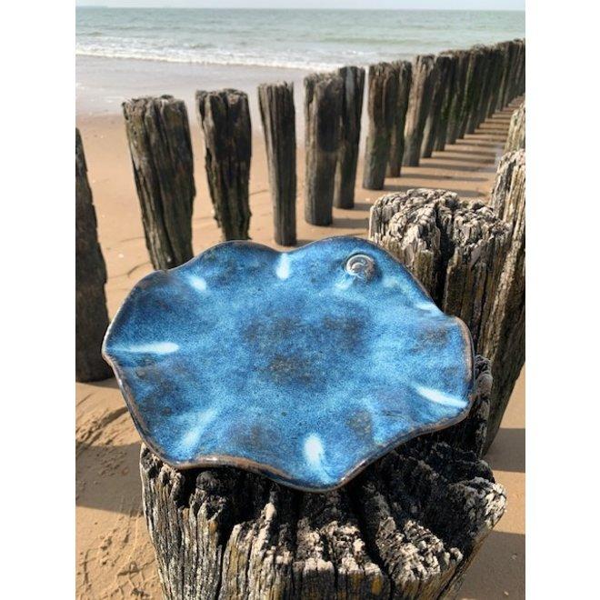 Un plat creuse fait avec les mains en argile Belge red et son magnifique glaçage à feu Floating bleu.